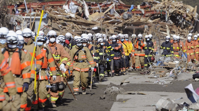 Firefighters march toward the assigned areas for search for victims of the March 11 quake and tsunami in Rikuzentakata, Iwate Prefecture, Friday morning, March 18, 2011. (Kyodo News)