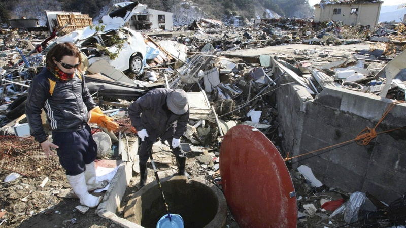 Survivors use a plastic bucket to get water from a well at the devastated town of Yamada, northeastern Japan, on Friday, March 18, 2011. (Yomiuri Shimbun / Takashi Ozaki)