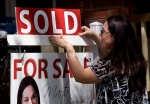 A real estate agent puts up a 'sold' sign in front of a house in Toronto. (Darren Calabrese / THE CANADIAN PRESS)