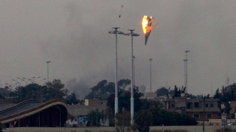 A warplane of Gadhafi's forces is seen being shot down with the pilot parachuting out of it over the outskirts of Benghazi, eastern Libya, Saturday, March 19, 2011. (AP / Anja Niedringhaus)