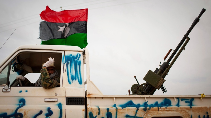 A Libyan rebel gestures as he arrives with heavy weapon on top of his truck to the frontline near Sultan, south of Benghazi, Libya, Friday, March 18, 2011. (AP / Anja Niedringhaus)