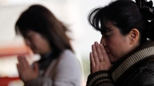 Tourists pray at Sensoji Temple Saturday, March 19, 2011 in Tokyo, Japan. (AP / Eugene Hoshiko)
