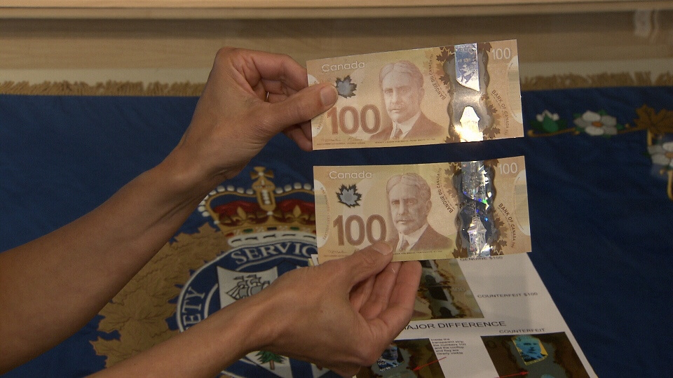 In this undated photo, police in New Westminster hold up a counterfeit $100 polymer bill (top) and a genuine one.