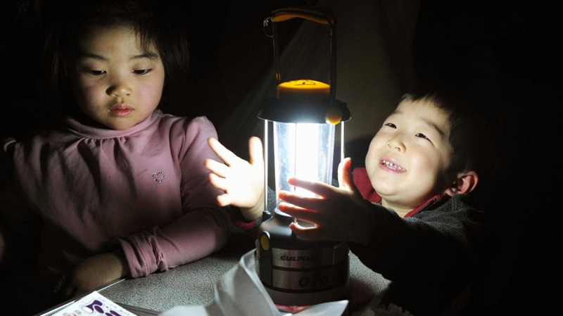 Earthquake survivors react to a just distributed lamp at an evacuation centre which became dark following sunset in the devastated town of Minamisanrikucho, northeastern Japan, Saturday, March 19, 2011 following last week's massive earthquake and resulting tsunami. (AP / Kyodo News)