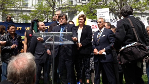 Flanked by protesters and surrounded by media, Denis Coderre officially announced his candidacy for the mayoralty of Montreal on May 16, 2013 (CTV Montreal/Tania Krywiak)