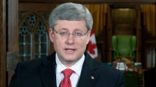 Prime Minister Stephen Harper speaks with the media the foyer of the House of Commons on Parliament Hill in Ottawa, Friday March 18, 2011. (Adrian Wyld / THE CANADIAN PRESS)