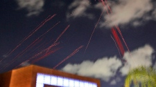 Tracers from anti aircraft fire guns are seen above the hotel where foreign media and government officials are staying in Tripoli, Libya, as explosions rock the city Monday, March 21, 2011. (AP / Jerome Delay)