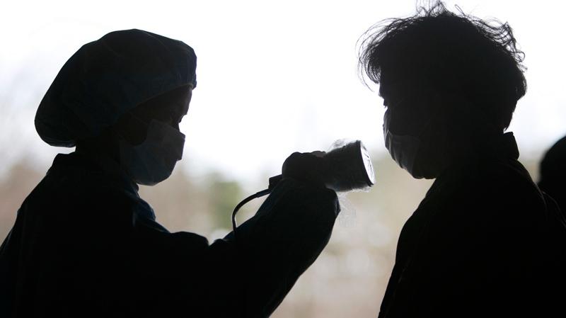 A woman is screened at an evacuee centre for leaked radiation from the damaged Fukushima nuclear facilities, Monday, March 21, 2011 in Fukushima, Fukushima prefecture, Japan. (AP / Wally Santana)