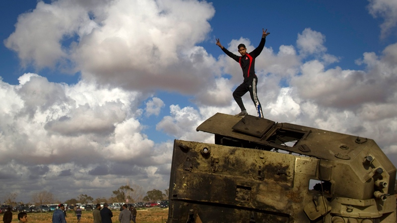 A Libyan boy reacts while standing on top of a destroyed military vehicle belonging to the forces of Moammar Gadhafi in the outskirts of Benghazi, eastern Libya, Sunday, March 20, 2011. (AP / Anja Niedringhaus)