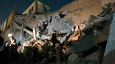 Libyan soldiers survey the damage to an administrative building hit by a missile late Sunday in the heart of Moammar Gadhafi's Bab Al Azizia compound in Tripoli, Libya, as they are pictured during an organized trip by the Libyan authorities, early Monday, March 21, 2011. (AP / Jerome Delay)