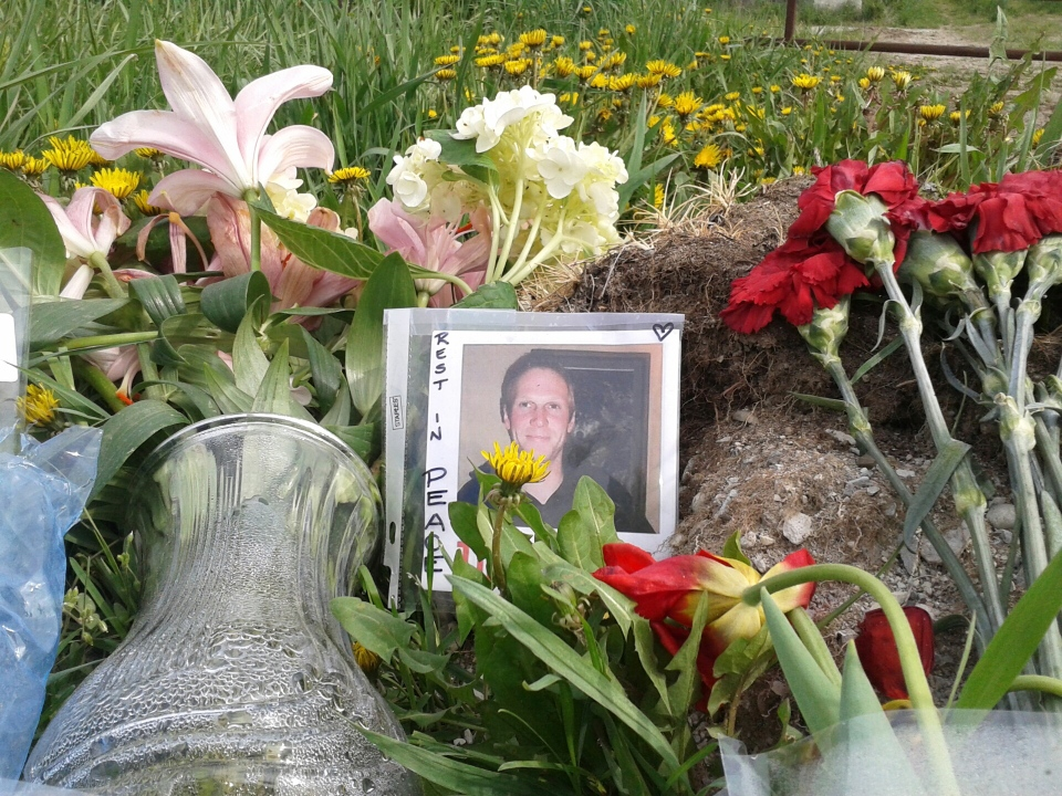 Flowers and photos sit at a memorial to Tim Bosma outside a farm in North Dumfries, Ont., on Friday, May 17, 2013. (Terry Kelly / CTV Kitchener)