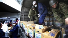 Japan Ground Self-Defense Force members unload boxes containing drinking water from their truck as the relief supply arrive at the village office in Iitate, Fukushima Prefecture, Japan, Monday, March 21, 2011. (AP / The Yomiuri Shimbun, Koichi Nakamura)