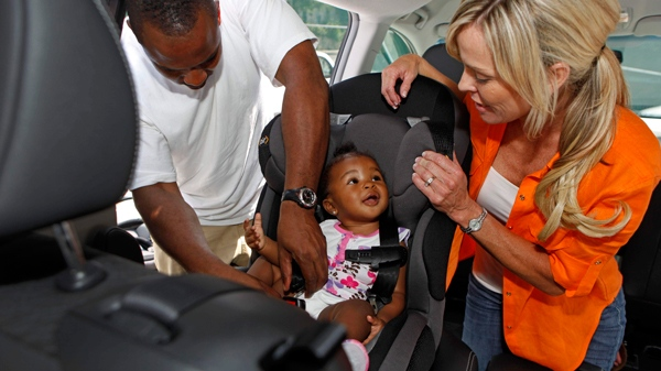 Child safety expert Kimberlee Mitchell, right, installs a car seat for Kennedy Word, 8 months, as father Kendall Word, looks on during a car seat check hosted by Dorel Juvenile Group, AAA, and the New York City Department of Transportation in New York, Friday, July 16, 2010. (David Goldman / AP Images for Dorel Juvenile Group)
