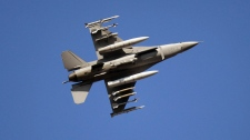 An F-16 jet fighter flies over the NATO airbase in Aviano, Italy, Monday, March 21, 2011. (AP / Luca Bruno)