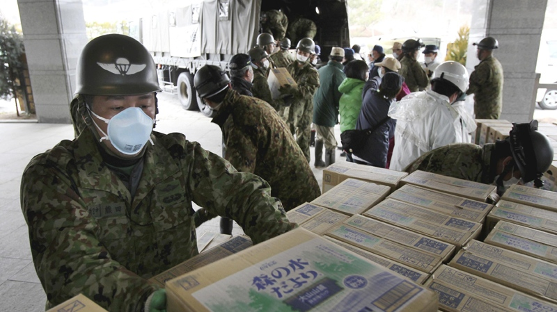 Japan Ground Self-Defense Force members carry boxes containing drinking water to the village office in Iitate, Fukushima Prefecture, Japan, Monday, March 21, 2011. (AP Photo/The Yomiuri Shimbun, Koichi Nakamura)
