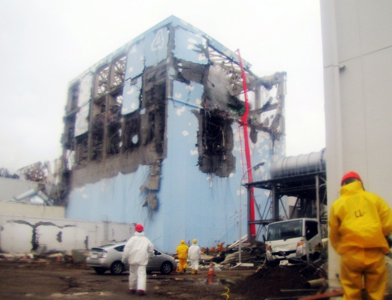 Workers in protective suits conduct cooling operation by spraying water at the damaged No. 4 unit of the Fukushima Dai-ichi nuclear complex in Okuma, northeastern Japan, Tuesday, March 22, 2011. (Tokyo Electric Power Co. via Kyodo News)