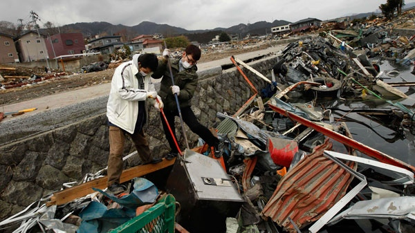 Local men try to break open a safe they said washed away from their restaurant in Ofunato, Japan, Tuesday, March 15, 2011. (AP / Matt Dunham)