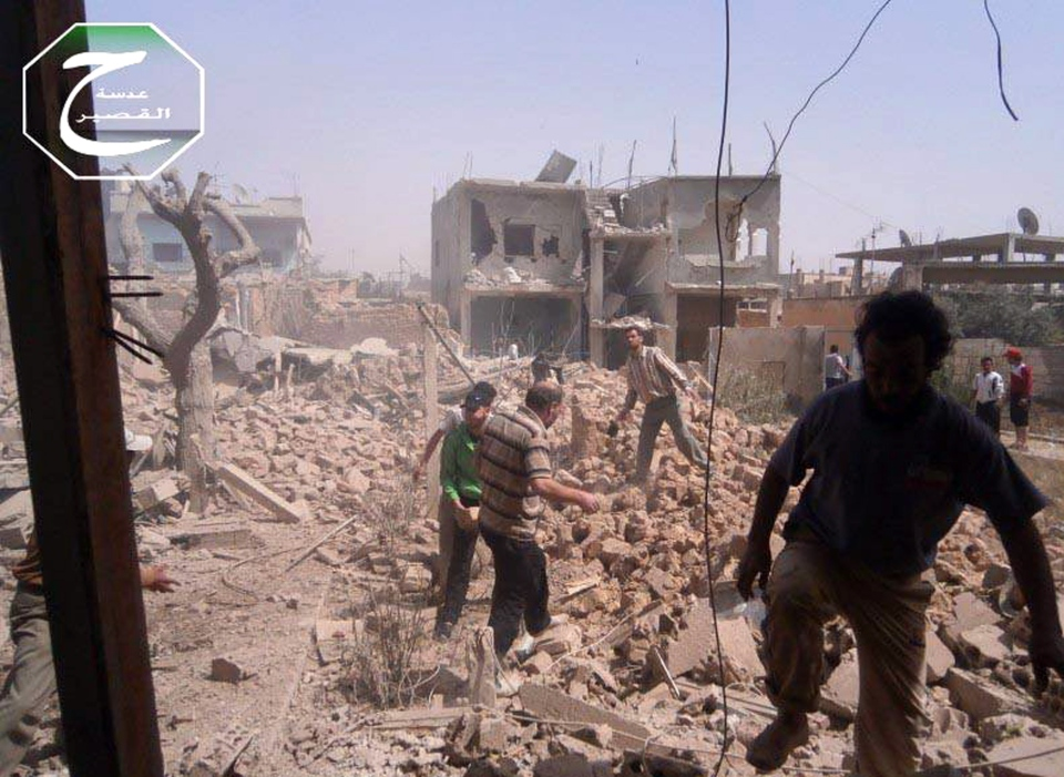 Syrians are seen inspecting the rubble of damaged buildings due to government airstrikes, in Qusair, Homs province, Syria on Saturday, May 18, 2013. (AP / Qusair Lens)