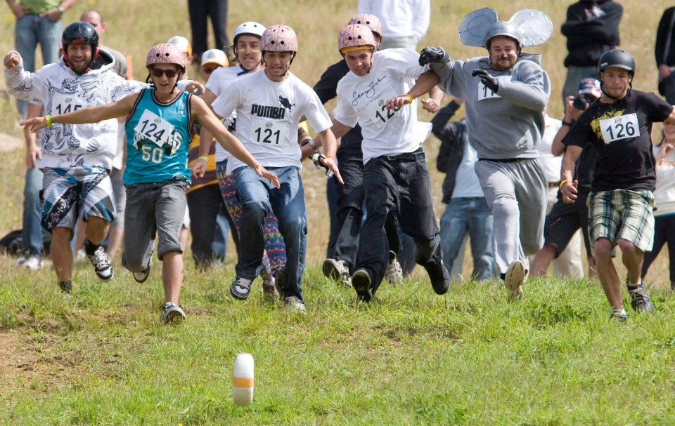 Competitors race downhill after an 5-kilogram wheel of cheese during the 2nd Annual Cheese Rolling Festival on Blackcomb Mountain in Whistler, B.C., Saturday, Aug. 15, 2009. (Jonathan Hayward / THE CANADIAN PRESS)