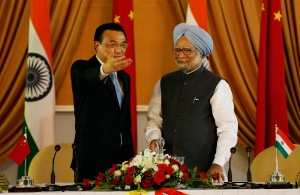 Chinese Premier Li Keqiang, left, speaks to Indian Prime Minister Manmohan Singh after a joint press briefing in New Delhi, India, Monday, May 20, 2013. (AP Photo/Saurabh Das)