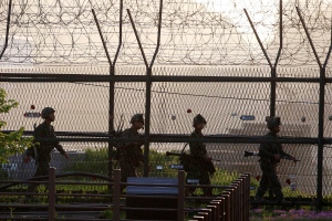 South Korean Army soldiers patrol along a barbed-wire fence near the border village of the Panmunjom in Paju, South Korea, Monday, May 20, 2103. (AP / Ahn Young-joon)