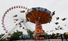In this June 13, 2012 photo, visitors ride on the ferris wheel and Wave Swinger at Chicago's nearly century-old Navy Pier. Clinton Shepherd, park operations manager at the Navy Pier, rode the tourist spot's Ferris wheel for more than 2 days over the weekend of May 18-19, 2013, bringing the world record for the longest ride to the birthplace of the amusement park favorite. (AP Photo/Charles Rex Arbogast, File)