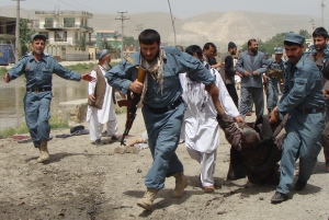 Afghan policemen evacuate a wounded person after a suicide bomber struck outside a provincial council headquarters in Pul-i-Khumri, Baghlan province, northern Afghanistan, Monday, May 20, 2013, killing the council chief and at least more than a dozen others, authorities said. (AP Photo/Jawed Basharat)