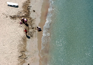 A family plays in the sand on a beach at the southern Athens suburb of Vouliagmeni, Thursday, April 20, 2006. Greece is basking in warm temperatures ahead of Orthodox Easter, on Sunday, April 23. (AP Photo/Thanassis Stvarkis)