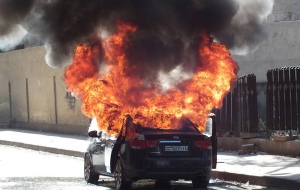 Flames rise from a car which was attacked by Syrian government forces, in Bustan al-Qaser neighborhood, Aleppo, Syria, Monday May 20, 2013. (Aleppo Media Center / AMC)