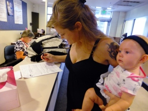 In this July 16, 2012, photo, Laura Fritz, 27, left, with her daughter Adalade Goudeseune fills out a form at the Jefferson Action Center, an assistance center in the Denver suburb of Lakewood. (AP / Kristen Wyatt)