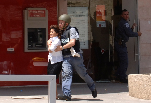 An Israeli woman is taken out of a bank in the town of Beersheba, Monday, May 20, 2013. (AP Photo/Dudu Greenspan)