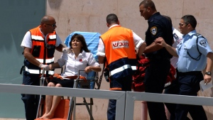 An Israeli woman is taken out of a bank in the town of Beersheba, Monday, May 20, 2013. (AP / Dudu Greenspan)