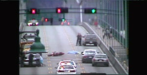 A toppled motorcycle can be seen on the Lions Gate Bridge with what appears to be a body with a tarp over it lying nearby. (CTV)