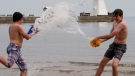 Kyle Lynch (left) and friend Alex Durocher splash each other as they enjoy the mild weather on the beach in Port Dover, Ont., Saturday, May 18, 2013. (Dave Chidley / THE CANADIAN PRESS)