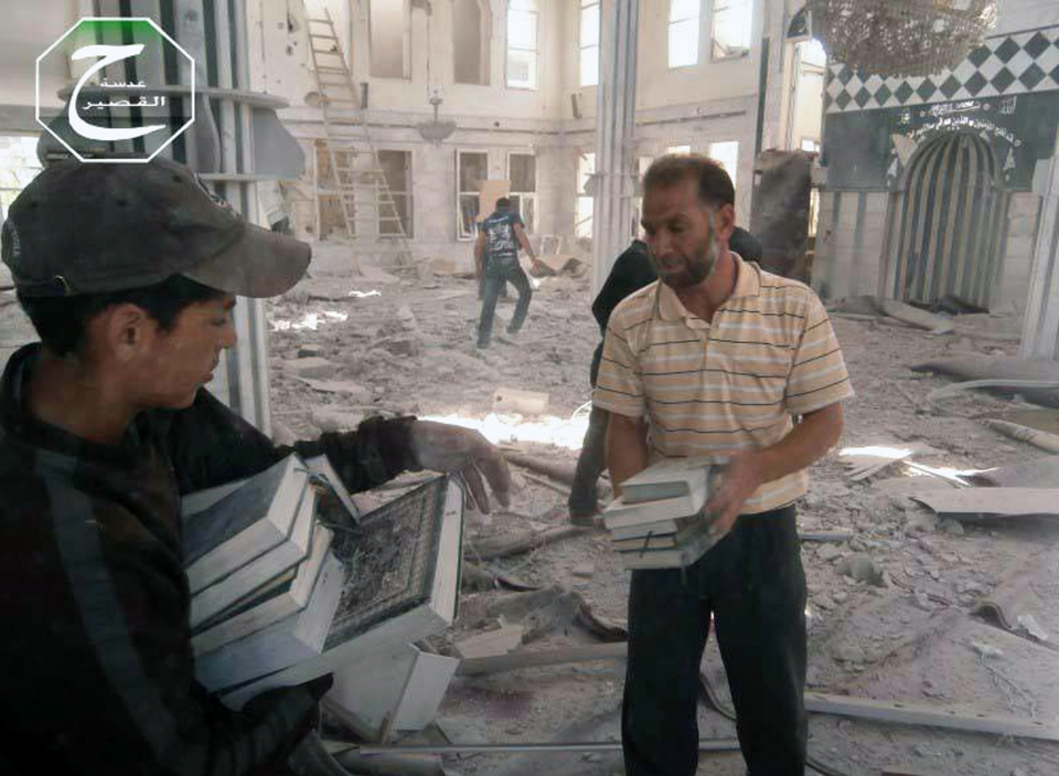 Syrian men are seen carrying copies of the Muslim holy book, the Quran, inside a bombed mosque in the town of Qusair near the Lebanon border, Homs province, Syria, Tuesday, May 21, 2013. (AP / Qusair Lens)