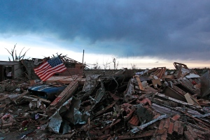 An American flag blows in the wind at sunrise atop the rubble of a destroyed home a day after a tornado moved through Moore, Okla., Tuesday, May 21, 2013. (AP / Brennan Linsley)