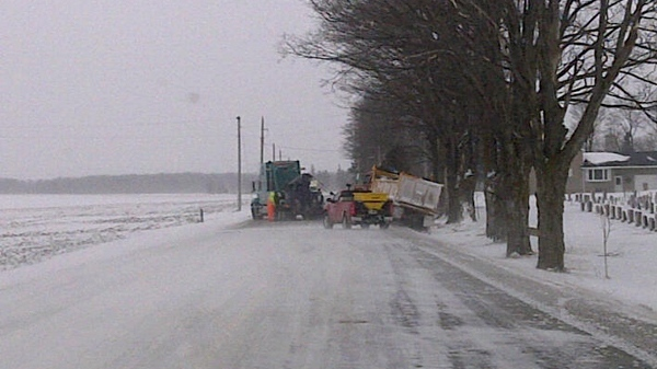 A dump truck is being helped out of the ditch after an overnight storm on Line 16, southeast of Tavistock, Ont., Wednesday, March 23, 2011.