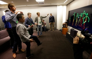 A group of visiting journalists try out the improved motion-detecting capabilities of the new Kinect controller for Microsoft's next-generation Xbox One entertainment and gaming console system, Tuesday, May 21, 2013, in Redmond, Wash. (AP Photo/Ted S. Warren)