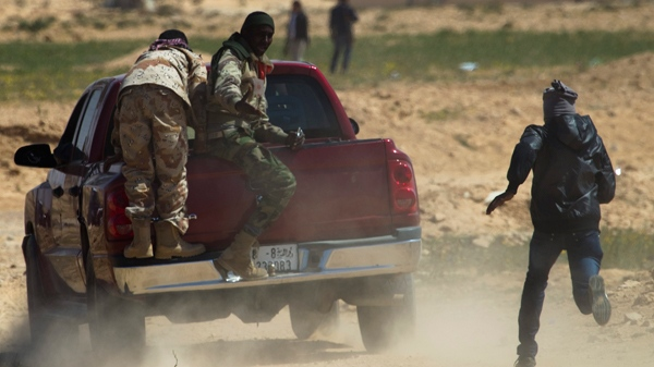 Libyan rebels run to take cover as mortars from Moammar Gadhafi's forces are fired on them on the frontline near Zwitina, the outskirts of the city of Ajdabiya, south of Benghazi, eastern Libya, Wednesday, March 23, 2011. (AP / Anja Niedringhaus)
