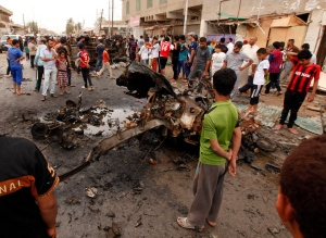 Civilians inspect the scene of a car bomb attack in Kamaliyah neighborhood, a predominantly Shiite area of eastern Baghdad, Iraq, Monday, May 20, 2013. (AP / Hadi Mizban)
