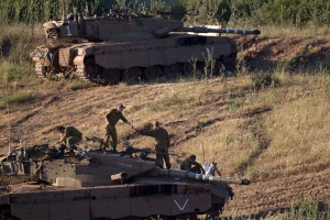 Israeli soldiers work on top of a tank in a position in the Israeli controlled Golan Heights, on the border with Syria, Tuesday, May 21, 2013. (AP / Ariel Schalit)