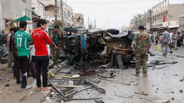 Iraqi security forces members and civilians gather at the scene of a car bomb attack in Kamaliyah neighborhood, a predominantly Shiite area of eastern Baghdad, Iraq, Monday, May 20, 2013. (AP / Hadi Mizban)