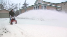 A resident in digs out after an overnight storm in Kitchener, Ont. on Wednesday, March 23, 2011.