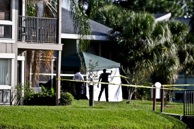 Investigators stand outside an apartment complex where a man was fatally shot when a team of FBI agents swarmed his home early  in Orlando, Fla. on May 22, 2013. (AP / John Raoux)
