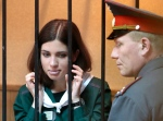 Nadezhda Tolokonnikova, a member of the feminist punk band, Pussy Riot, listens from behind bars at a district court in Zubova Polyana 440 km Southeast of Moscow in Russia's province of Mordovia, Friday, April 26, 2013. (AP Photo/Mikhail Metzel)