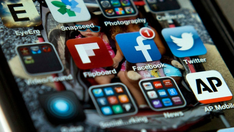 An iPhone shows the Twitter and Facebook apps, among others. (AP Photo/Evan Vucci)