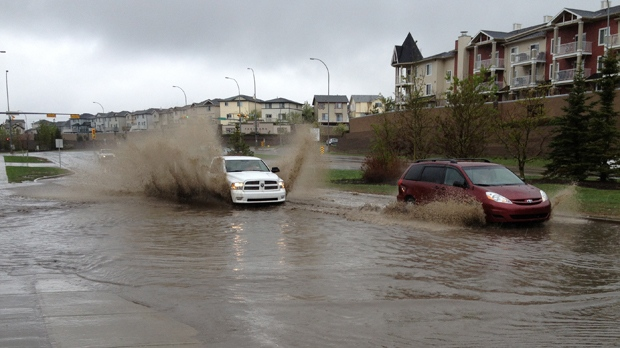 Vehicles make their way through a massive puddle on Harvest Hills Blvd. near Country Hills Way N.E. on Friday afternoon