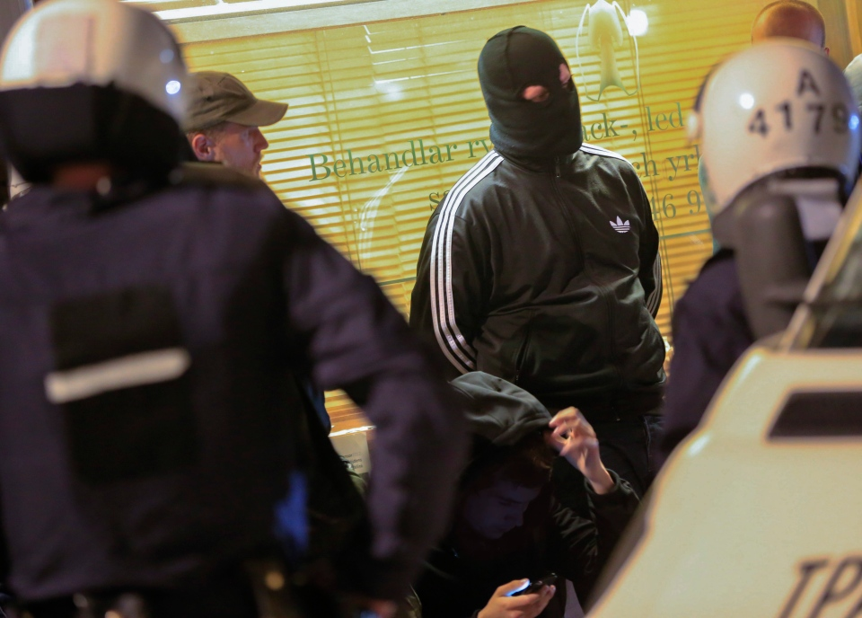 Masked men are lined up against a wall by riot police in a Stockholm suburb early Saturday morning May 25, 2013, as about 200 right-wing extremists cruised around town in their cars looking for trouble on the sixth straight night of riots. (AP / Fredrik Persson)