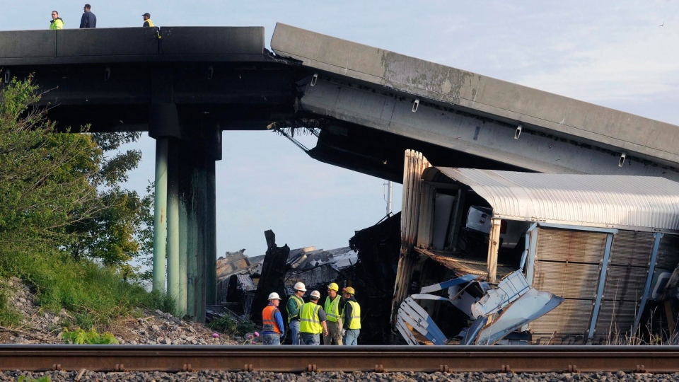 Emergency personnel investigate the Route M overpass after it collapsed onto the railroad tracks, in Rockview, Mo., Saturday, May 25, 2013. (The Southeast Missourian, Fred Lynch)
