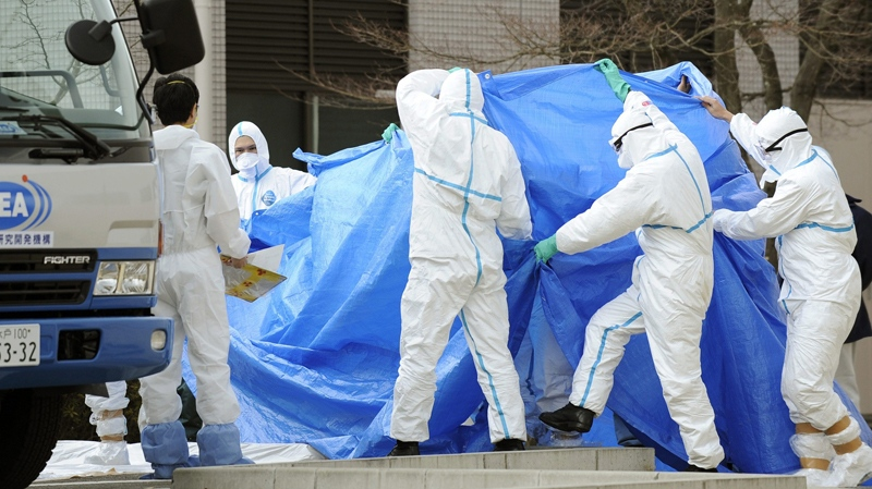 Workers, who stepped into radiation-contaminated water during Thursday's operation at the Fukushima Dai-ichi nuclear plant, are shielded with tarps before receiving decontamination treatment at a hospital in Fukushima, northeastern Japan Friday, March 25, 2011. Later the men were transferred to a radiology medical institute for further treatment. (Kyodo News)